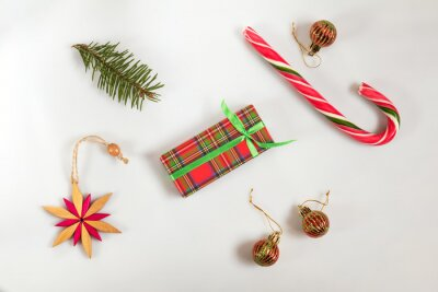 Christmas and New Year composition. Christmas gift, fir tree branches, candy cane, wooden star. Flat lay on white background, top view