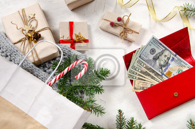 Christmas shopping, big seasonal sale. rustic background with gifts, money in red purse and shopping bag with presents. Top view