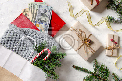 christmas shopping concept. big sale. seasonal rustic background with gifts money wallet and shopping bag with presents. Top view