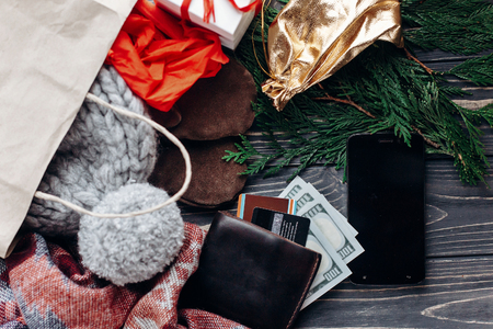 christmas shopping concept. big sale. seasonal rustic background with phone with empty screen money wallet and bags of  presents. advertising app with space for text
