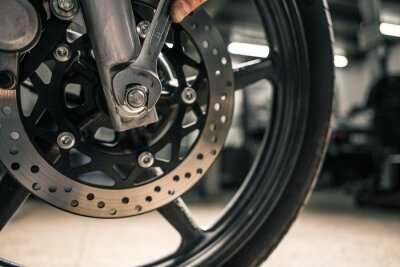 Canvas print Close up of man's hand holding mounting wrench near the motorcycle's vehicle.