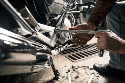 Canvas print Close up of man's hands with motorcycle in garage