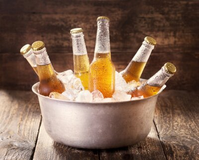 Canvas print cold bottles of beer in bucket with ice