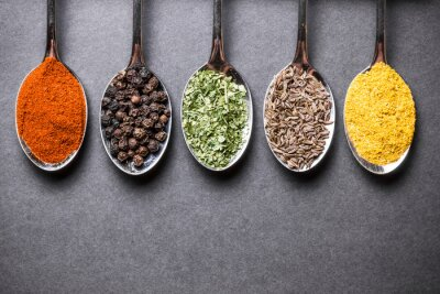 Canvas print Colorful spices on metal spoons on black rough rock surface.