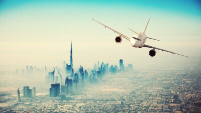 Canvas print Commercial airplane flying over modern city