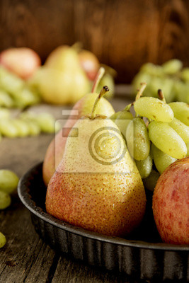 Crop Plate with pears and apples. Autumn fruits. Vertical photo.