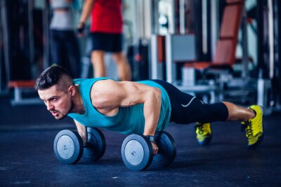 Canvas print Crossfit instructor at the gym doing pushups