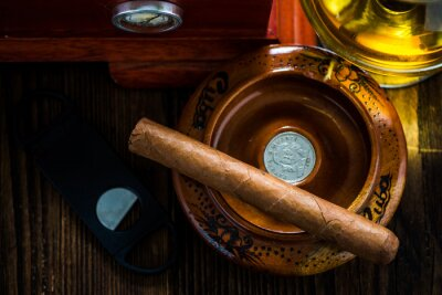 Canvas print Cuban cigar in ashtray with glass of cognac ad humidor