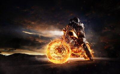 Canvas print Dark motorbiker staying on burning motorcycle in sunset light