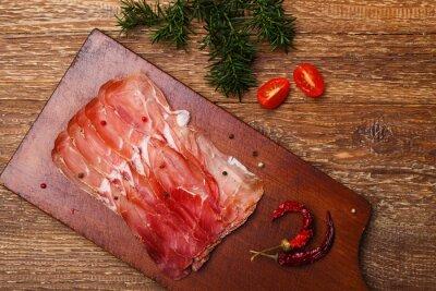 Canvas print Delicious prosciutto ham on a wooden board with spices.