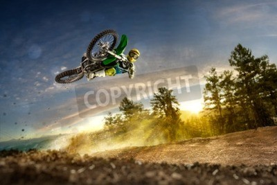 Canvas print Dirt bike rider is flying high in evening