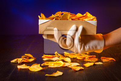 Dried oranges. Dried pear. Dried apples. Dried fruits in a box. In his hand a box of dried fruit. snack