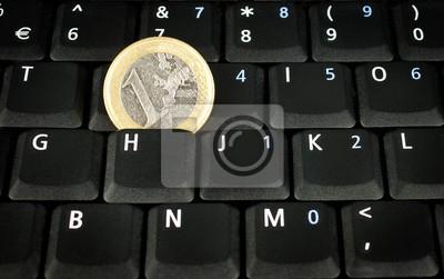 euro coin on laptop keyboard