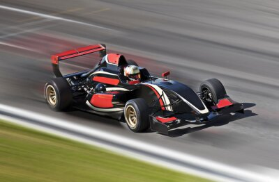 Canvas print F1 race car racing on a track with motion blur