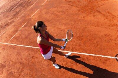 Canvas print Female tennis player serving a tennis ball