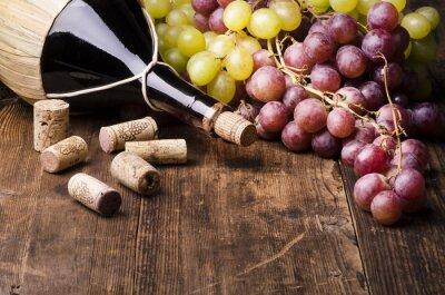 Canvas print fiasco di vino con uva e turaccioli su tavola di legno
