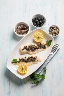 Canvas print fish fillet with black olives capers and anchovies