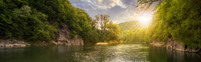 Canvas print forest river with stones on shores at sunset