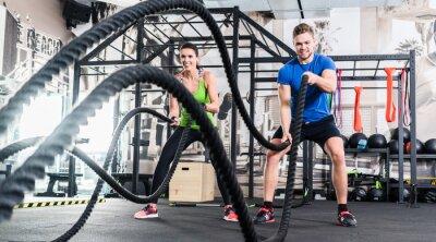 Canvas print Frau und Mann im Fitnessstudio mit battle rope