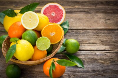 Canvas print Fresh and juicy citrus fruits in the basket on the rustic table