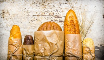 Canvas print Fresh bread wrapped in paper. On rustic background.
