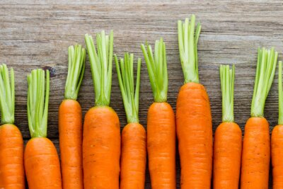 Canvas print Fresh carrots bunch on rustic wooden background.
