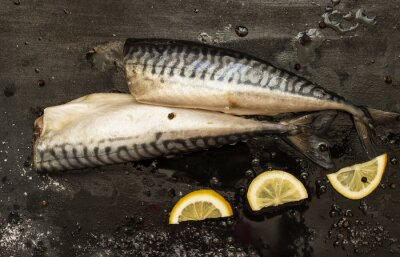 Canvas print Fresh cut mackerel slices of lemon, salt, pepper on a black background
