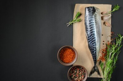Canvas print Fresh fish mackerel on dark background from above. Fish with aromatic herbs and spices  - healthy food, diet or cooking concept