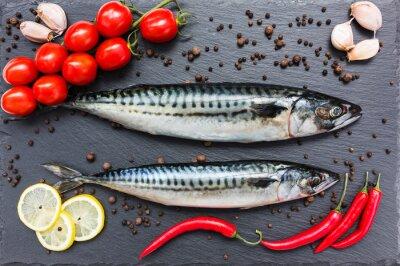Canvas print Fresh mackerel fish, chili pepper, lemon, tomatoes, garlic on a slate cutting board. Top view