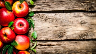 Canvas print Fresh red apples with green leaves on wooden table.