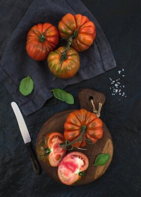 Canvas print Fresh ripe hairloom tomatoes and basil leaves on rustic wooden board over black stone background.