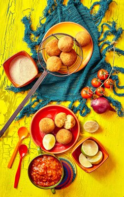 Canvas print Fried bolhinos and garnishes in bowls and plates