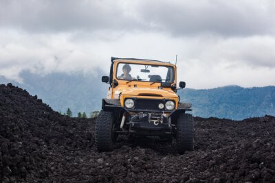 Canvas print Frontside view of a curly-haired driver in yelow offroad vehicle parked at the top of a valley with volcanic rock and mountains in Bali, Indonesia