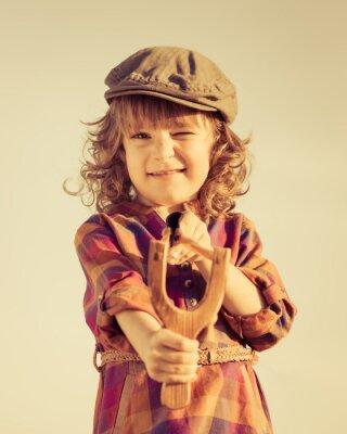 Canvas print Funny kid shooting wooden slingshot