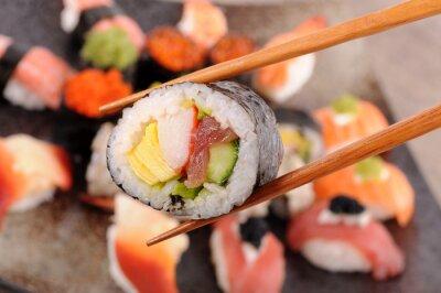 Canvas print Futomaki sushi held by chopsticks