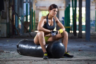 Canvas print girl seating on boxing bag