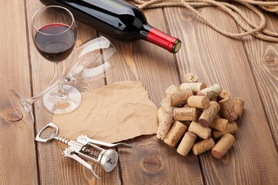 Canvas print Glass of red wine, bottle and corkscrew on rustic wooden table