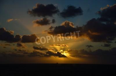 glowing sunset on sea with ship on horizon