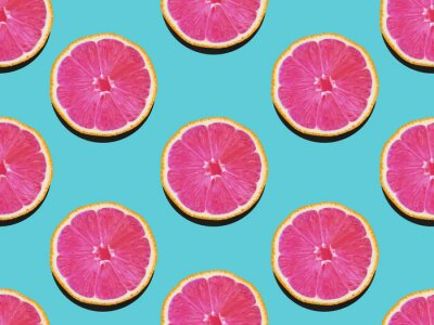 Canvas print Grapefruit in flat lay Fruity pattern of grapefruit with pink flesh on a turquoise background Top view Modern flat lay photo pattern in pop art style