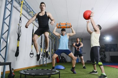 Canvas print Group of people in action doing crossfit exercises