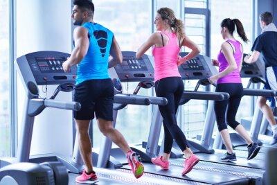 Canvas print Group of people running on treadmills