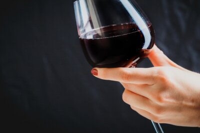 Canvas print Hand holding glass of red wine on dark grey background