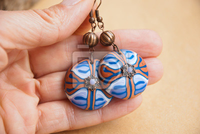 Handmade jewelry from polymer clay. Floral Ethnic earrings with unique pattern in woman hand. Fashion jewelry.Still life in boho style. Trendy accessory.