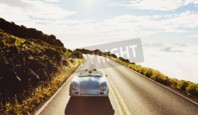 Canvas print Happy Couple Driving on Country Road in Classic Vintage Sports Car