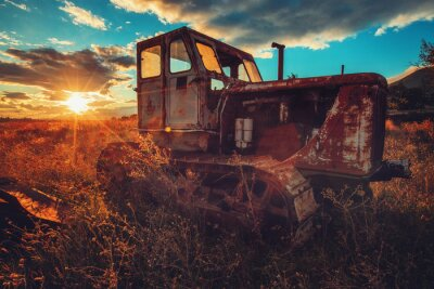Canvas print HDR image of old rusty tractor in a field. Sunset shot