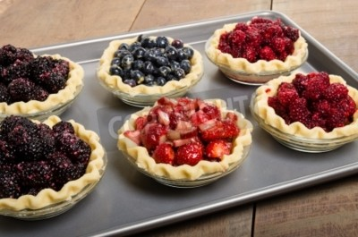 Homemade fresh fruit pies on a tray made with strawberries raspberries blueberries blackberries