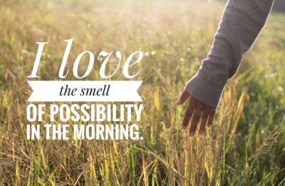 Canvas print Inspirational motivational quote - I love the smell of possibility in the morning. With warm morning light over the field & young woman hand touch the leaves of paddy in field background.