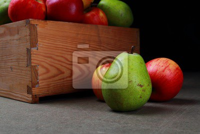 Juicy pears and apples. Autumn fruits in a wooden box.