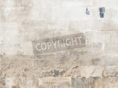 light rough surface of the old wall made of natural rough stone beige with dirty black seams and oil paints drawn down arrow and number 10