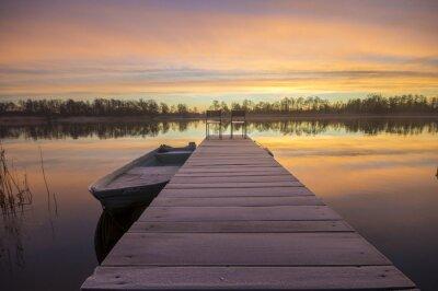 Canvas print łódka zacumowana zimą do drewnianego pomostu